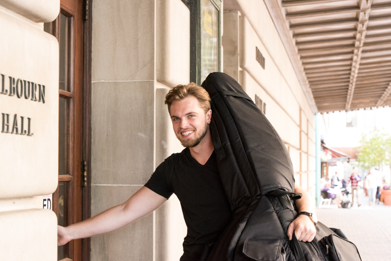 Music student with instrument entering Eastman School of Music