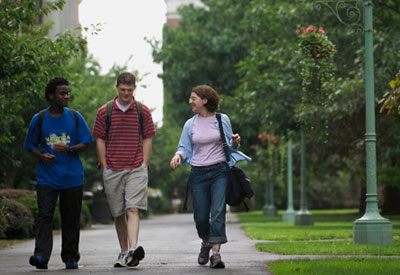 three people walking on campus
