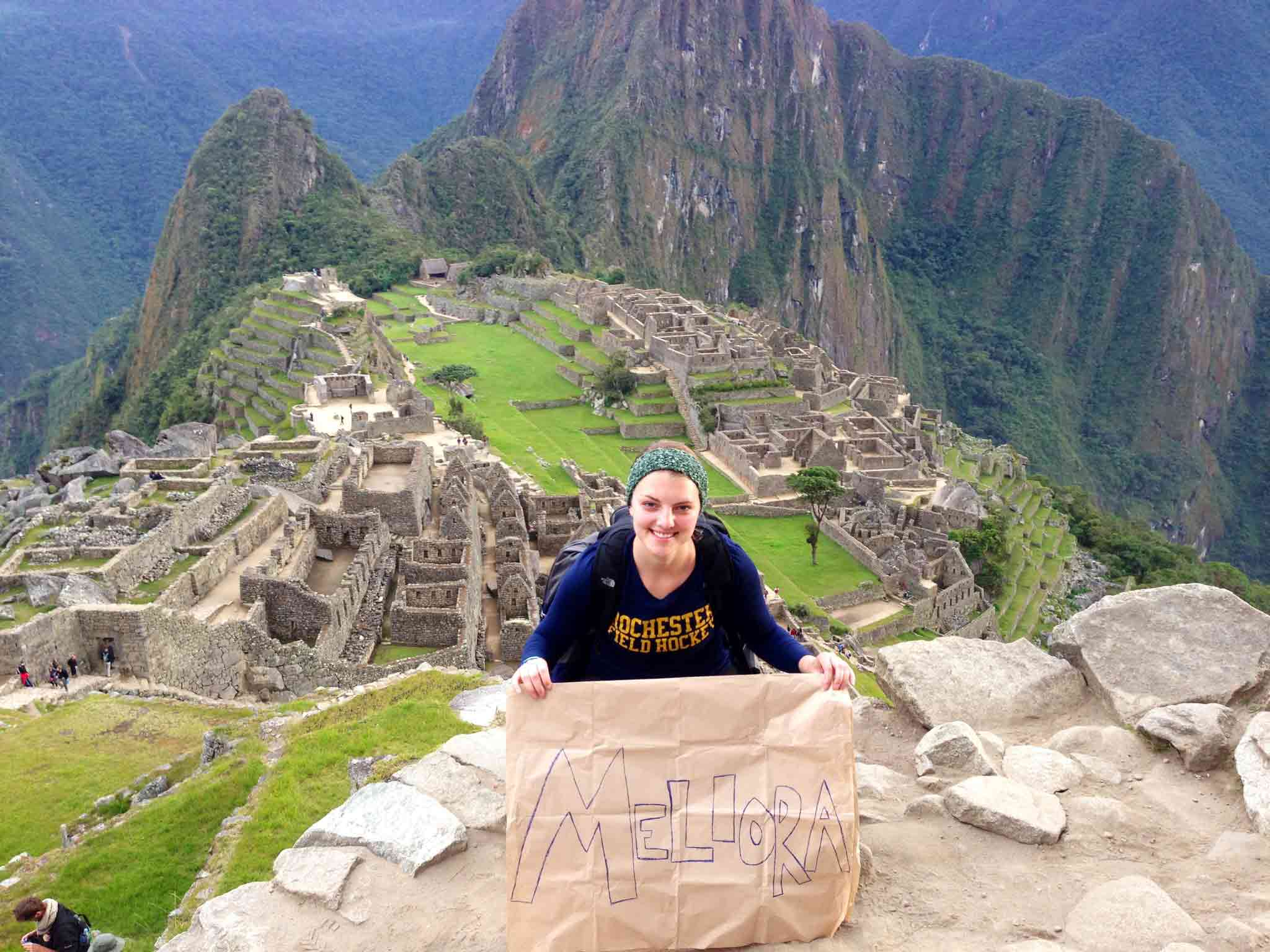student holds sign saying MELIORA on top of Machu Picchu