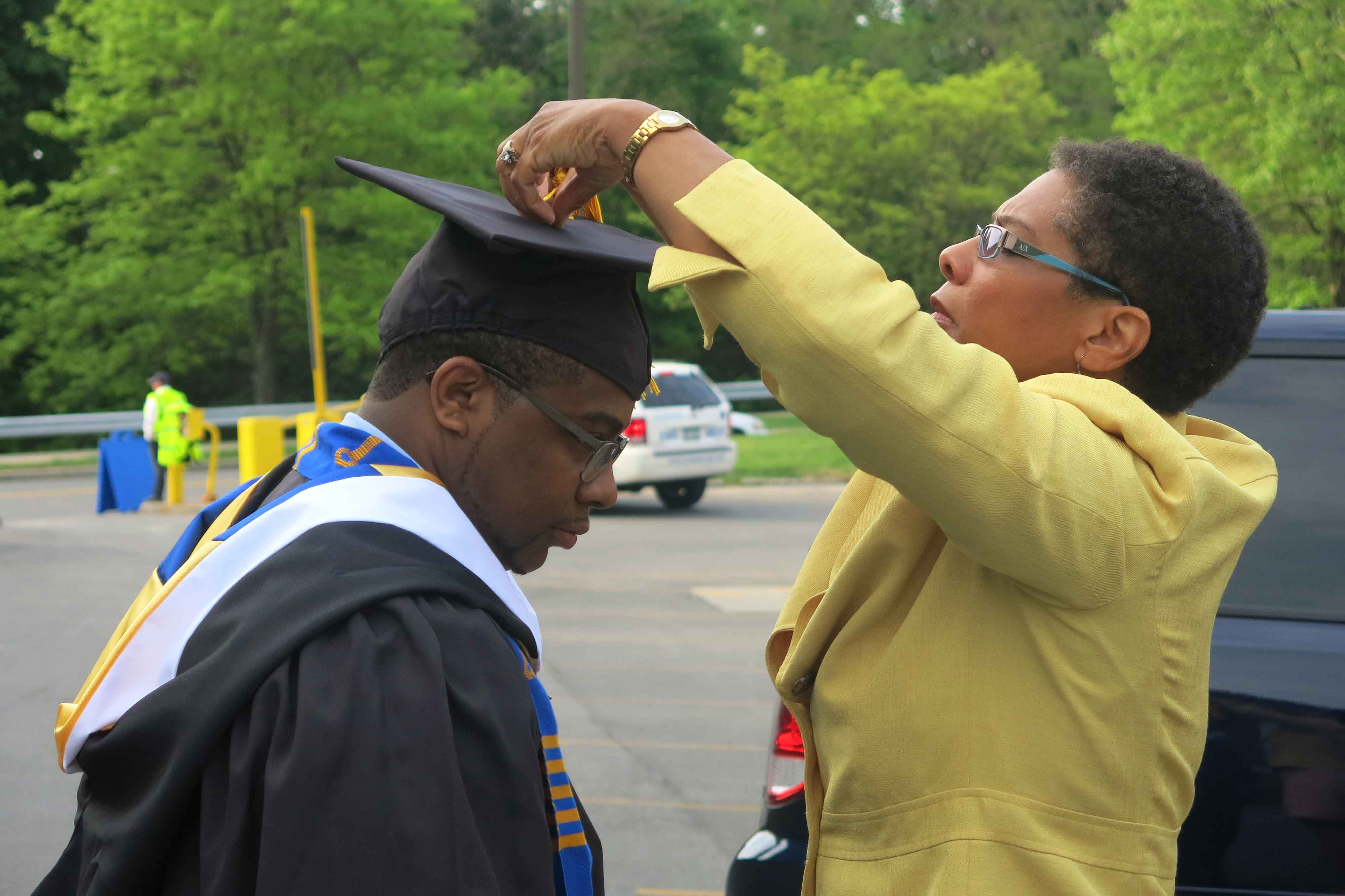 mom adjusting son's graduation cap