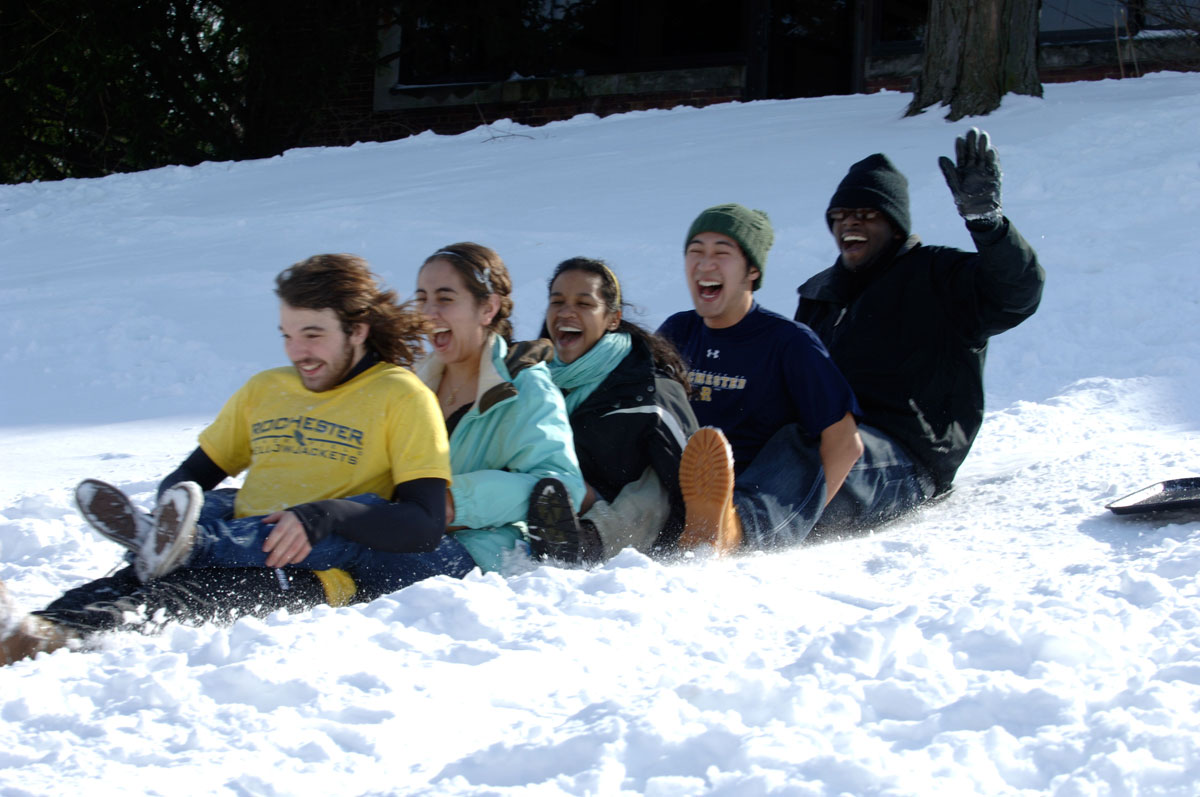 students sledding down a hill