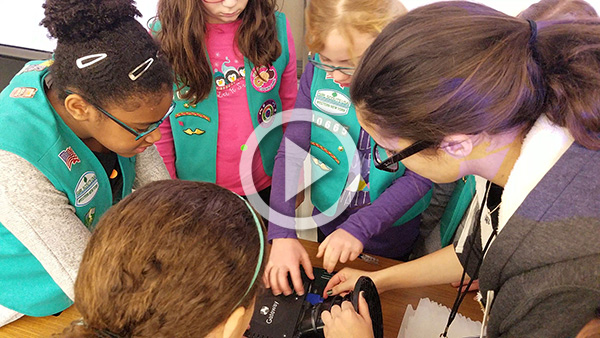 female student showing Girl Scouts the inner workings of a computer