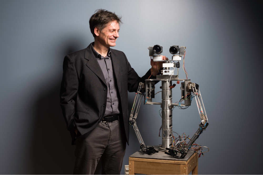 Faculty robotics researcher standing next to robot head and upper torso at University of Rochester