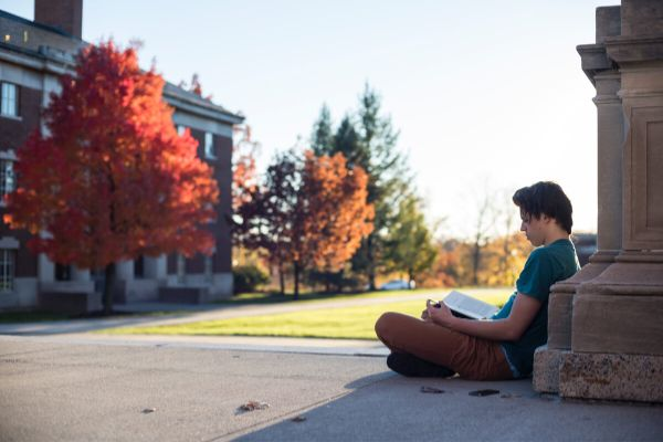 Student sitting on campus of Unversity of Rochester