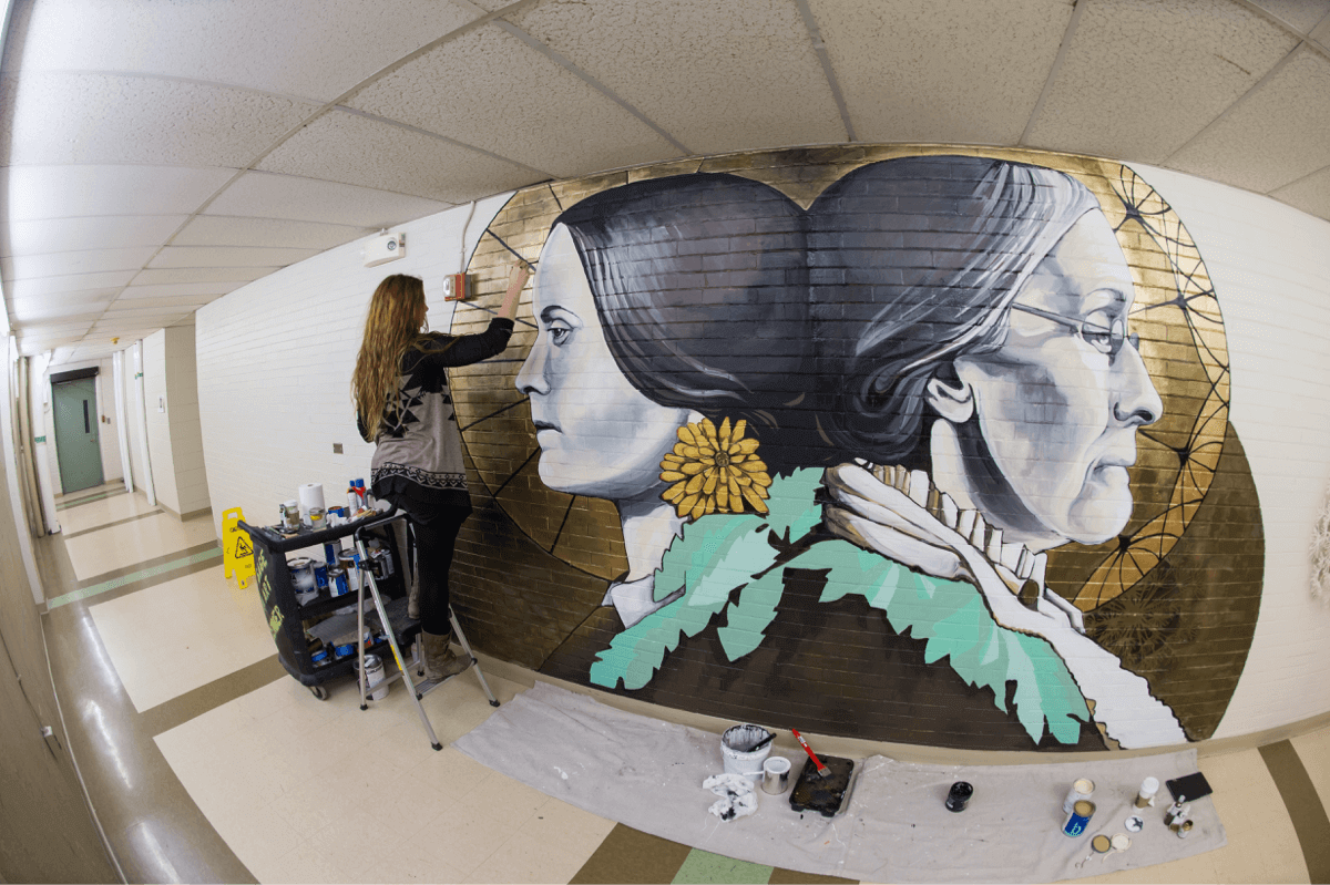 Artist painting a mural at University of Rochester