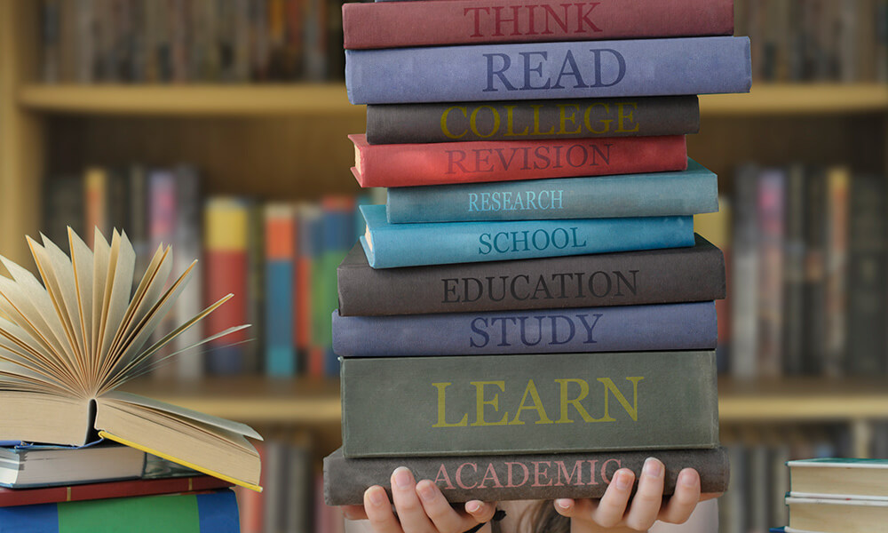 image of student holding stack of books.