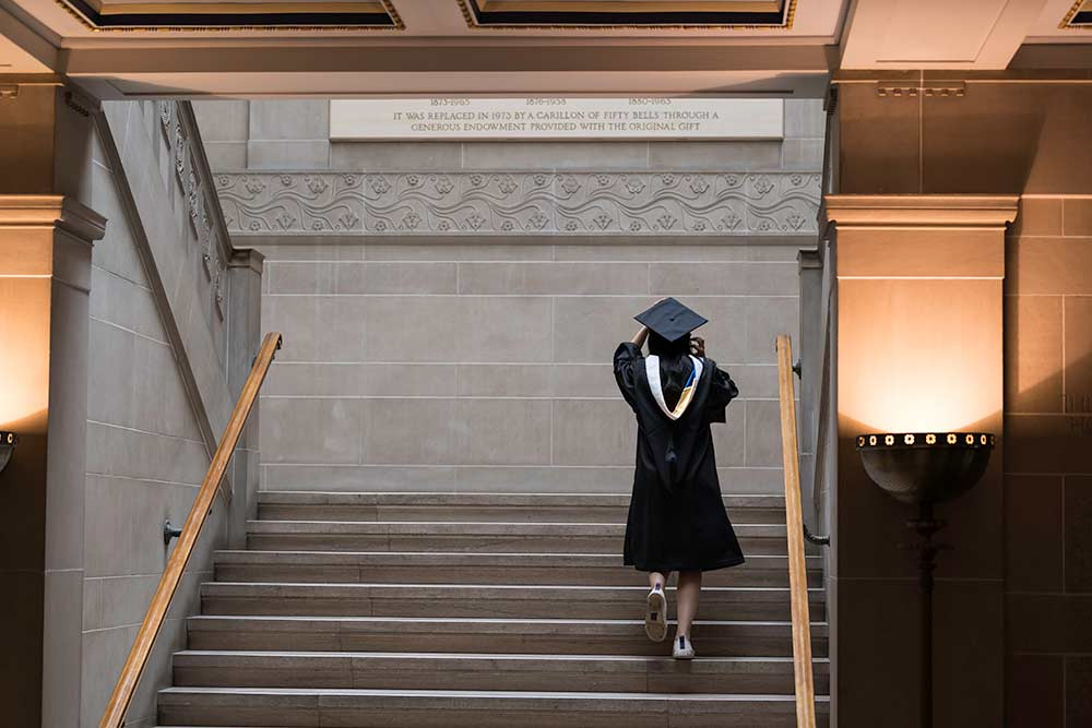 Student walks up stairs of Rush Rhees Library in cap and gown