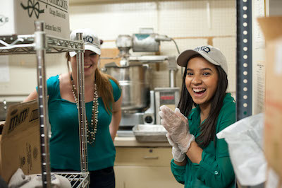 Two student employees smiling while making fudge