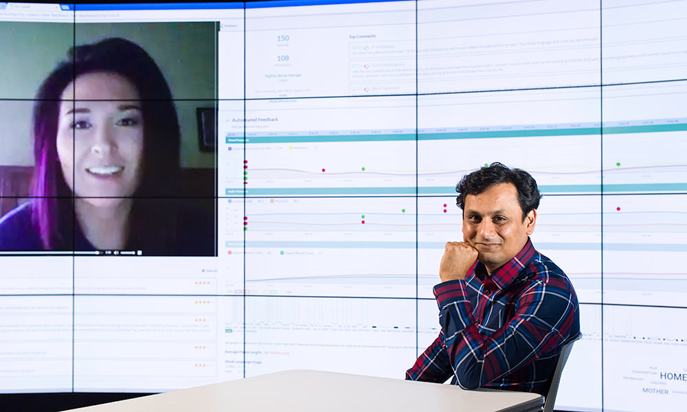 Ehsan Hoque in front of large computer screen